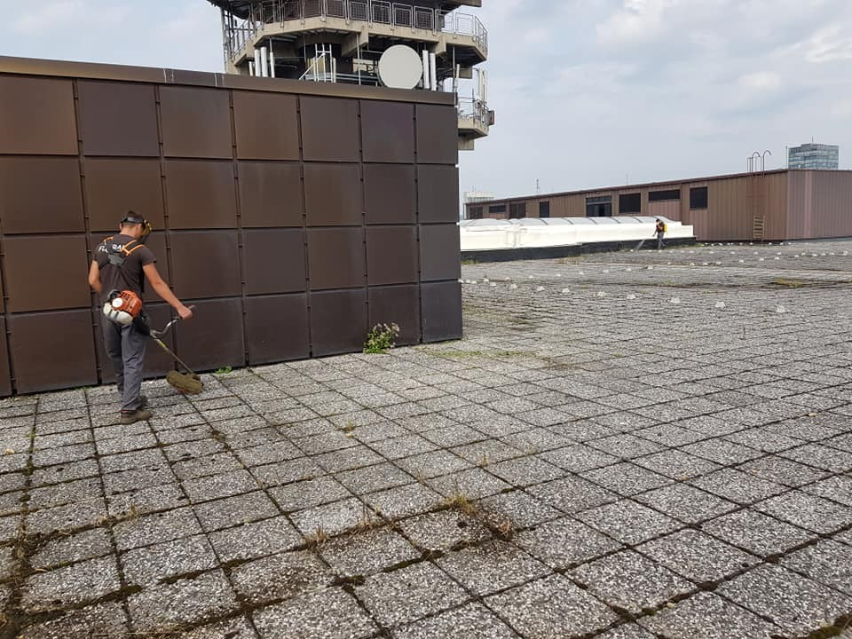 Uklanjanje korova i kemijsko tretiranje elemenata ravnog krova na vrhu zgrade.